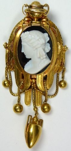 European hand crafted 14k yellow gold and cameo brooch pendant by Lambert Goldsmith's, England. Finely crafted to show a cameo with high raised white bust over black oval plaque. Cameo is mounted in large gold frame with urn to top and hanging beads on chains. Has hanging handled amphora vase. 19th century /Estimate $7,000 – $9,000