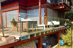 Garde-corps en verre feuilleté trempé posés sur la terrasse en bois d'un client. Garde-corps fixés avec des attaches faites sur mesure. Conception et pose réalisée par Vitralux Bradtke S.à r.l..