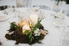Centrepiece (5) 3 Cylinder Vases with Ivory pillar candles surrounded with moss and ivory flowers.