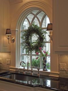 Elegant #christmasdecor in kitchen with exquisite arched window over sink hung with #christmaswreath. #holidaydecor
