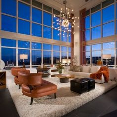 Contemporary penthouse with stunning view. The conversation area of this living room sits on a custom raised platform covered in shag carpet, thusly, the view can be enjoyed from the seated position. Built-ins surrounded by windows wrap the corner area, which includes a bar, reclaimed wood shelves that slide out for display, and sculpture. Automated woven shades can filter light at the touch of a button. Missoni fabrics throughout, including the beautiful open weave drapery panels.