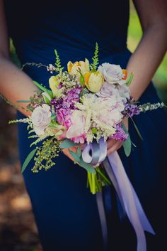 A bridesmaid in blue holds a colorful spring bouquet with a streaming purple ribbon.