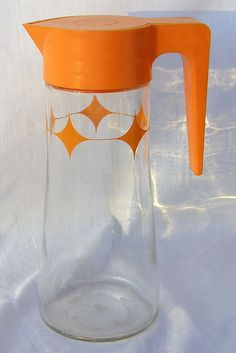Vintage Anchor Hocking Glass Orange Juice Pitcher.    This juice or lemonade carafe is clear glass with an orange diamond pattern and features a removable orange plastic lid and handle. The screw-on lid has a hinged flip-top opening which is operated by depressing it with one's thumb or finger. The bottom of the pitcher has an Anchor Hocking makers mark. The lid states: * DO NOT SHAKE * DO NOT SHAKE *