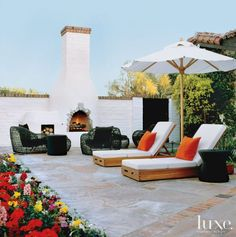 Resting poolside and gazing over a raised bed of flowers are two armless chaises from David Sutherland paired with a side table from Walters Wicker. A grouping of Balou open-weave furniture from Janus et Cie draws closer to the fireplace for cool desert nights.