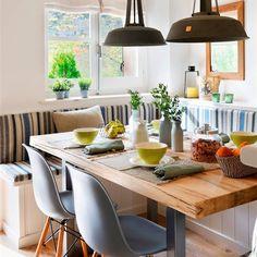 Comedor con banco en U a medida, cojines a rayas blanco y azul, sillas Eames, mesa con sobre de madera y patas metálicas y lámparas de techo