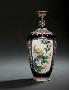 A CLOISONNÉ VASE  MEIJI PERIOD (LATE 19TH CENTURY)  Worked in silver wire and coloured enamels on a dark blue ground with four shaped panels of various flowers and foliage including irises, roses and chrysanthemums, bordered by brocade designs on translucent grounds, copper gilt mounts