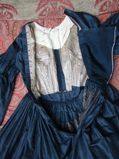 Back opening and inside bodice of 1840s/50s black dress. Shows the darts at the front and an added section of cloth at the centre back opening to make the dress bigger