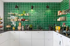 Lekfullt kök med vita skåpsluckor som matchas stilrent med en mycket tilltalande och slitstark, Dektonskiva på 12 mm. Köket har varsamt renoverats med tidstypisk färgsättning (20-tal), vitt/svart/grönt och med grönt italienskt handgjort kakel ovanför arbetsytorna.