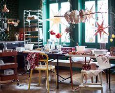 Ein langer Tisch voller Backutensilien wie Schüsseln Glaskaraffen mit Milch, Geschirrhandtüchern und Schürzen