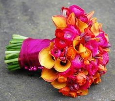 Designed by Planet Flowers. Bouquet Hot pink and orange calla lilies and ranunculus.