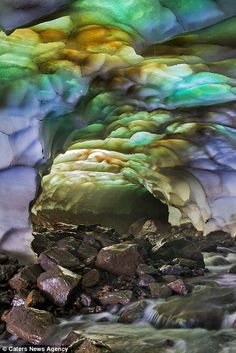 Rainbow: The caves are lit up in dazzling greens, blues and purples...