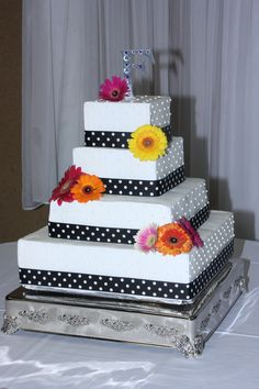 White wedding cake with Gerber daisies - Fake dummy cake with white buttercream frosting. Black and white polka dot ribbon on bottom of each tier along with gerber daisies on the cake. Bride didn't care for cake, so she  had cheesecakes instead.