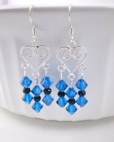 These gorgeous blue chandelier earrings are made with the high-quality, popular capri blue swarovski beads. These earrings make a beautiful blue statement with a touch of black to bring out the rich blue color. These earrings will brighten your day or someone else's day! Comes in a cute organza bag ready for gifting.  LENGTH: 2 inches total (from ear wire to lowest bead)