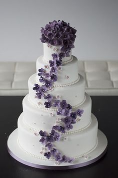 Maybe use the concept, but not this cake exactly. 4 tiers instead of five. Separate the top two from the bottom two. Have the top of this cake (the flowers) in the center in between the two halves. Maybe find a figurine topper. Oh, and not purple, but blue flowers instead (and prob. different flowers).