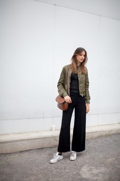 Cropped black pants with Adidas and a green bomber jacket.