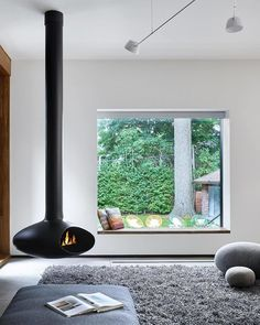 From Front to Back, This Toronto Home Literally Merges Heritage and Modernism - Photo 2 of 3 - The living space that features a freestanding fireplace looks out through a seated window that perfectly frames the yard. Suspended Fireplace, Hanging Fireplace, Freestanding Fireplace, Fireplace Windows, Modern Fireplace, Fireplace Design, Interior Design Inspiration, Decor Interior Design, Interior Design Living Room