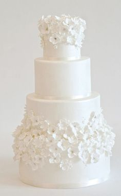 Classic white wedding cake decorated in mini white flowers; Featured Cake: Heartsweet Cakes