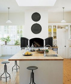 A crisp kitchen with open shelving and a drool worthy pizza oven. Lonny