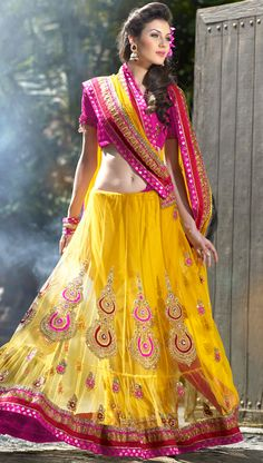 It is color this season and bright shaded suits are really something that is totally in vogue.   This yellow net lehenga style saree is nicely designed with embroidered patch work is done with zari, sequins, stone, beads and lace work.   Saree gives you a singular and dissimilar look.   Contrasting magenta blouse is available.   Slight color variations are possible due to differing screen and photograph resolution.