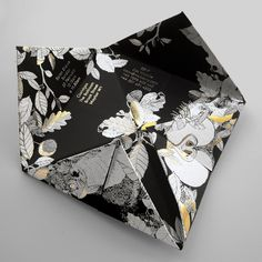 'Fortune teller' format: unfolds to reveal details of the Mulberry AW11 show. Ebony Colorplan, with illustrated woodland scene in white & gold foil. Packaged in rigid box with AW11 'feather' type foiled to lid. Feather type created by Craig Ward.