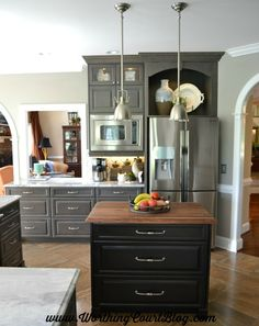 A fabulous remodeled kitchen with gray and black cabinets.  The display cabinet above the refrigerator makes a great place to showcase accessories || WorthingCourtBlog.com