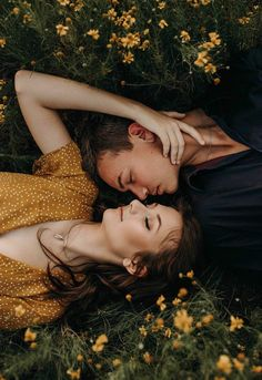 A girl and a boy laying in a field with their heads next to each other nearly kissing