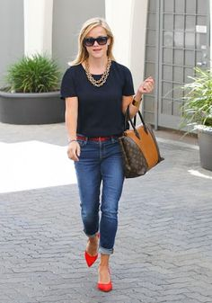 Reese Witherspoon dresses up a plain black tee with a statement necklace and red heels