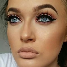 Bold cat eye + nude lip.