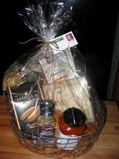 """""""Italian Dinner Basket""""  included in a rustic wire basket is pasta sauce, 2 boxes of bread sticks, 3 different pastas, Italian seasoning, Biscotti's, & a small canvas wall plaque that says """"LIVE WELL"""".  (see unwrapped pic)"""