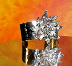 Handmade big flower bangle. The flower is 6cm wide and the material is silver.