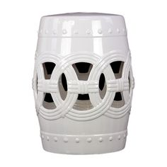 A garden stool in white featuring a cutout design stands out in an outdoor seating area or inside. | $170