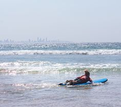 Paddling out with to catch some waves on a Gold Coast learn to surf lesson! #surfing #australia #goldcoast #activitiesforkids #summer #travel