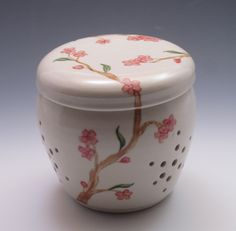 Porcelain Garlic Jar, handthrown and hand painted with cherry blossoms. Find your garlic quickly, rather than digging at the back of the fridge, in a pretty jar sitting within easy reach on your counter. A garlic jar is a handy place to store garlic, small onions and shallots and brings some beauty to your kitchen. The holes in the sides allow the bulbs to aerate, keeping them fresh and resistant to mildew. Because it is a covered jar, the darkness prevents garlic from sprouting too…
