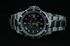1998 Rolex GMT Master II Men's wristwatch.  Stainless case and oyster bracelet, custom bezel made of ruby, sapphire and diamonds. Black face with illuminated hour positions and custom diamond encrusted case and lugs. Truly unique and beautiful watch. With box and papers. Guaranteed authentic Rolex. $11,999.99