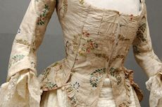 31-10-11  French Casaquin  c 1790    or Jacket of earlier brocaded silk with sprays of flowers in corals, peach, green, ivory silks on a silvery/ivory ground woven with small repeat spot motif, the front with large square neck, front opening, the linen lining with eyelet holes to both sides, the bottom squared and with a pleated frill edged with pale pink silk, three quarter shaped sleeves, the back with wide gussets narrowing to the waist and splaying out to the skirt, edged with…