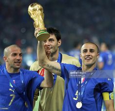 Italian defender Fabio Cannavaro (R) and forward Alessandro Del Piero hold up the World Cup trophy after Italy won their final 2006 World Cup football match against France at Berlin?s Olympic Stadium, 09 July 2006. Italy won 5-3 on penalties.