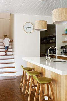 White chunky bench with timber cabinetry - and I love these pendant lights over the kitchen bench.