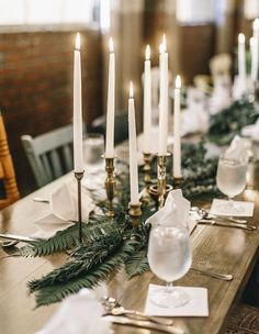 A green tablescape, with lots of leaves, vintage tall candlesticks and minimalist decor.