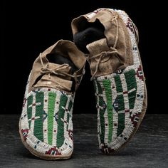 """Northern Arapaho Beaded Hide  sinew-sewn and beaded using colors of translucent green, pea green, rose, greasy blue, and white, length 11 in. late 19th century Included is a signed article by Mike Kostelnik discussing the attribution of these moccasins.   Kostelnik, Mike.  """"Northern Arapaho - ca 1890.""""  Whispering Wind. Fall-Winter 25.5 (1992):45. Provenance: From the Collection of John O. Behnken, Georgia Price Realized Including Buyer's Premium $900 09/23/2016"""