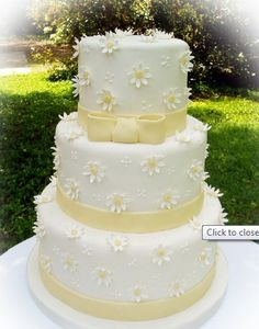 Daisy Wedding Cake...Minus that bow on top, just plain around the the bottom layer one...and possibly in the wedding color theme instead of that cream/tan color.