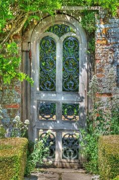 A garden gate with wrought iron elements. Lovvvveee.