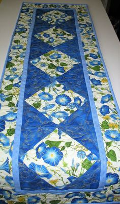 Christmas Table Runner, Metallic Silver,Blue made with fabric from Robert Kaufman Measures: 46 x 14.5 inches Made by Chris This gorgeous blue and white floral table runner is full of gold metallic and shades of palest blue to dark blue with touches of yellow and lovely green