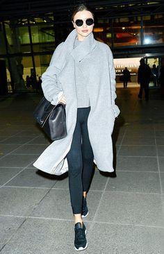Miranda Kerr wears a gray sweater, gray coat, leggings, a shoulder bag, round sunglasses, and sneakers