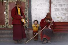 A boy puts his palms together as he rests with his family outside Jokhang Monastery in Lhasa, Tibet
