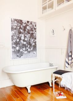 Black and white bathroom with poster-like art above tub and hanging robe