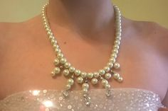 This beautiful pearl and crystal drop necklace will add elegance to any outfit. It is handcrafted with Swarovski drop crystals, premium glass pearls with a beautiful luster, silver plated beads, and a silver plated lobster clasp. It also has a 2 inch, pearl embellished extender chain. The drop crystals are clear and bright and sparkle with every movement.  It looks elegant with a formal dress, a pant suit, or to glam up a casual outfit.  Length: approximately 16 inches, not including the 2…