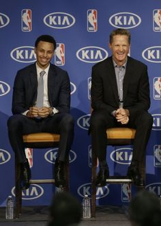Golden State Warriors guard Stephen Curry, left, and head coach Steve Kerr smile as they listen to speakers at a basketball news conference announcing Curry as the NBA's Most Valuable Player.