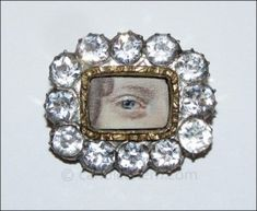 """A lady's blue eye painted in miniature on ivory, set in gold and surrounded by white sapphires. ¾"""" x ⅝"""" Late 18th century."""