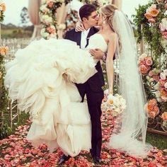 carrying her, bouquet in left hand, staring intently at each other