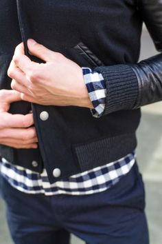 Men's casual fall outfit: black jacket and plaid shirt.